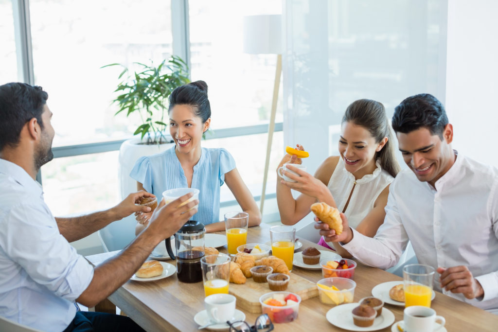 Business owners sitting around a table eating, laughing and enjoying a fresh breakfast with warm croissants and crisp cold orange juice. They have an LLC Operating Agreement yet have not discussed how to Dissolve an LLC or Remove an LLC Member.
